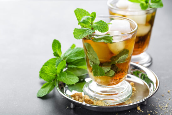 Mint Julep cocktail with bourbon, ice and mint in glass on black background